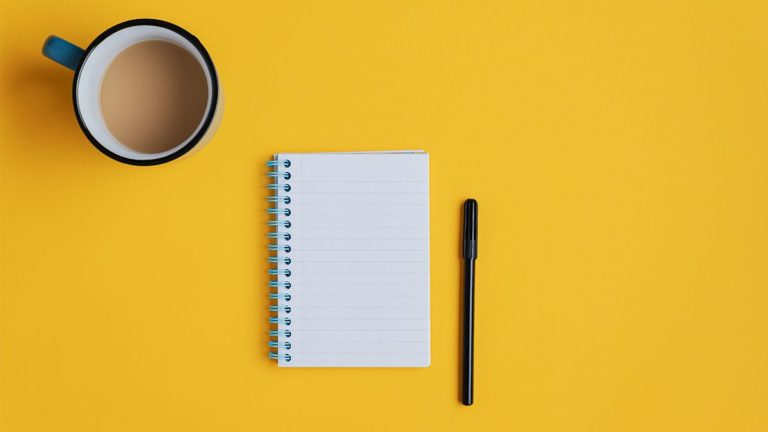 notepad and black pen with cup of coffee with cream on yellow background
