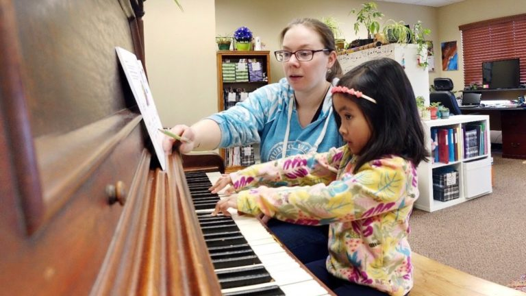 little girl practicing the piano next to her music teacher