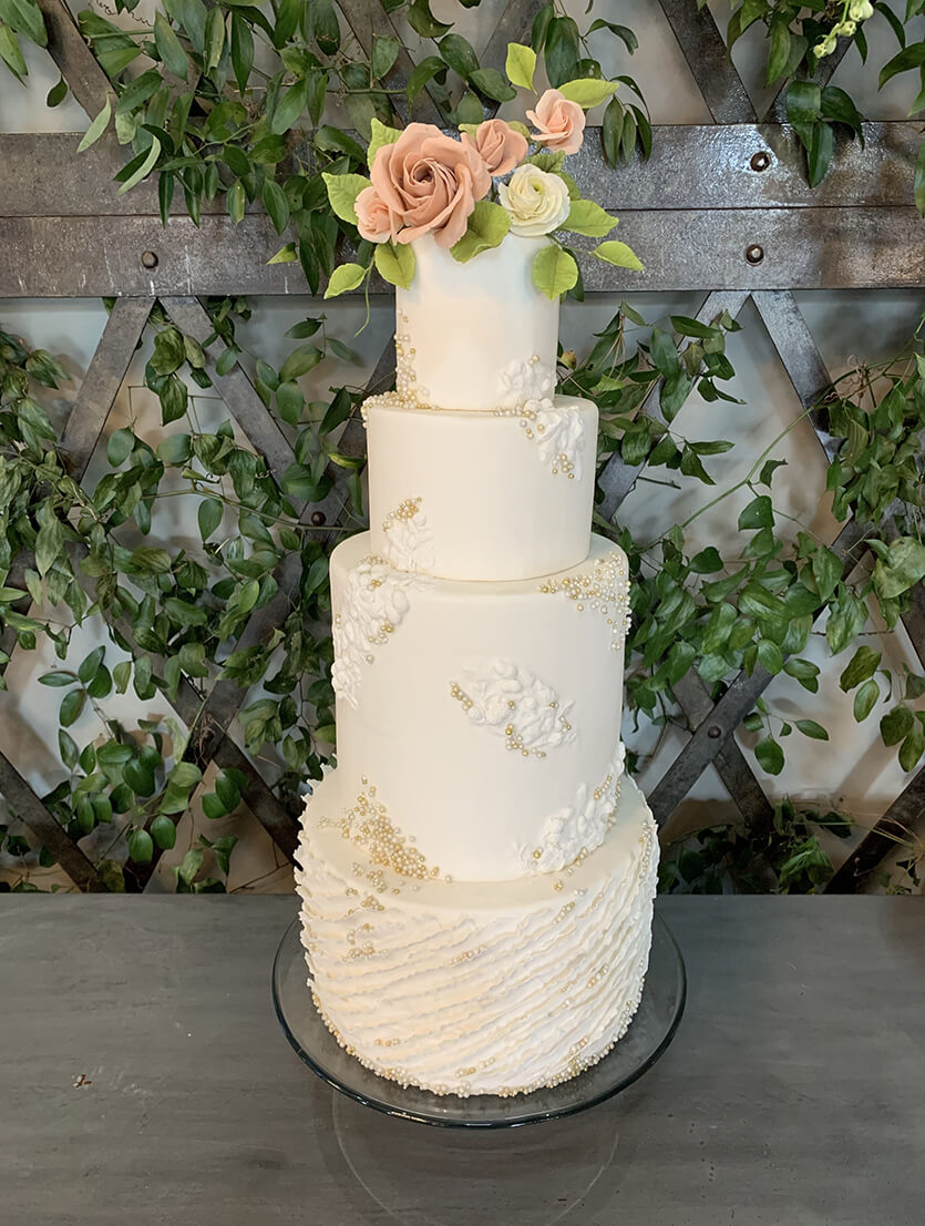 beautiful white 4-tier wedding cake with orange flowers on top