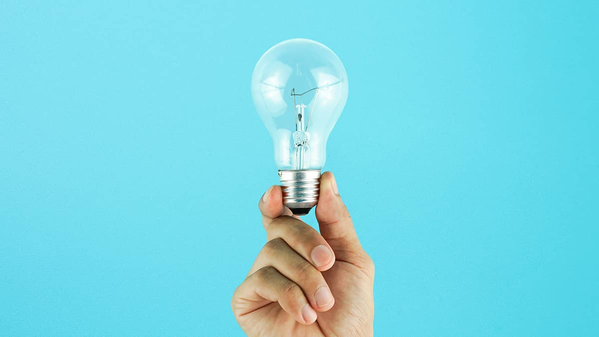 person holding lightbulb in front of blue background