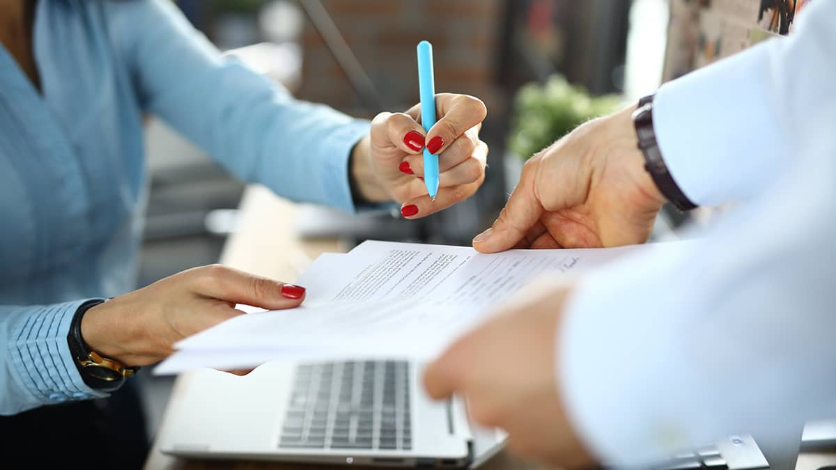 woman signing startup insurance documents